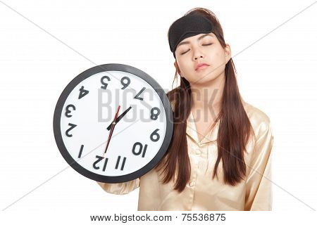 Sleepy Asian Girl With Eye Mask Hold A Clock Upside Down