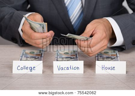 Businessman Saving Cash For College; Vacation And House