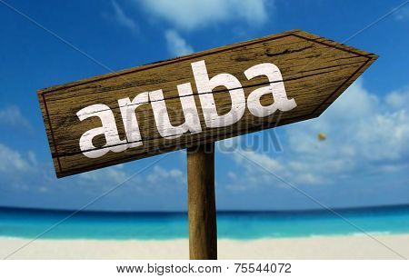 Aruba wooden sign with a beach on background