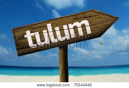 Tulum wooden sign with a beach on background