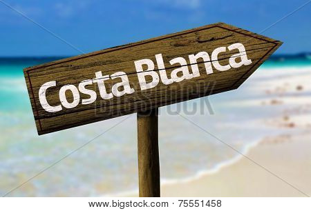 Costa Blanca wooden sign with a beach on background