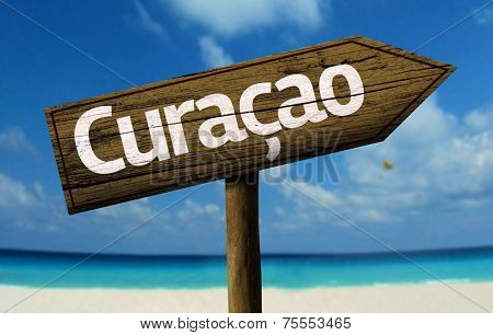 Curacao, Caribbean wooden sign with a beach on background