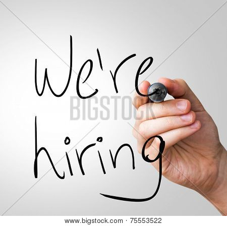 We're Hiring hand writing with a black mark on a transparent board