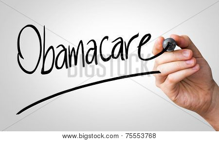 Obamacare hand writing with a black mark on a transparent board