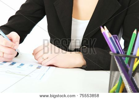 A woman at the desk writting on a paper, isolated on white.