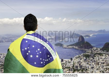 Brazilian holding a brazilian flag looks to the beautiful view of Rio de Janeiro, Brazil
