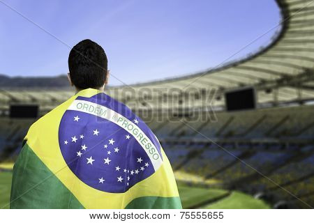 Brazilian holding a brazilian flag looks to the stadium