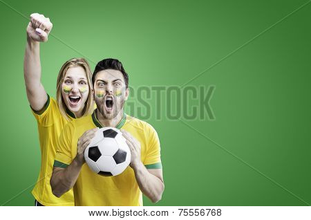 Brazilian couple celebrate on green background
