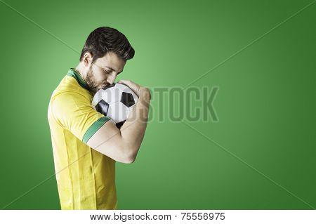 Brazilian man celebrates kissing a soccer ball on a green background