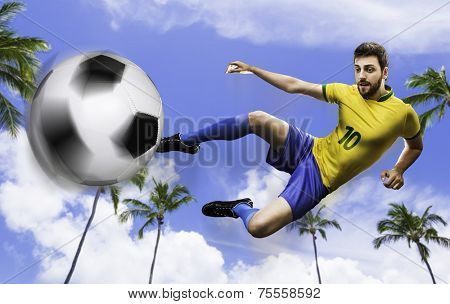 Brazilian soccer player in the jump kicks the ball a beautiful day