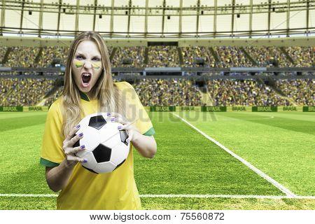 Brazilian fan holding a soccer ball celebrates on the stadium