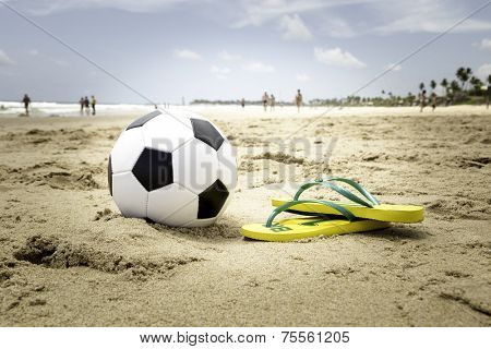 Soccer ball and a yellow Flip flop on the beach