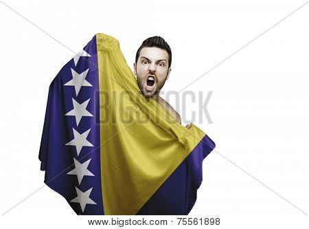 Fan holding the flag of Bosnia and Herzegovina celebrates on white background