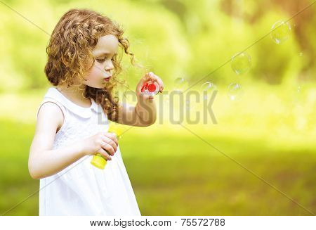 Cute Curly Little Girl Blowing Soap Bubbles Outdoors In Summer Day