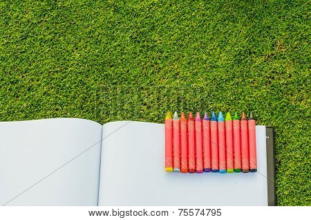Wax Crayons And Sketchbook On Fresh Spring Green Grass