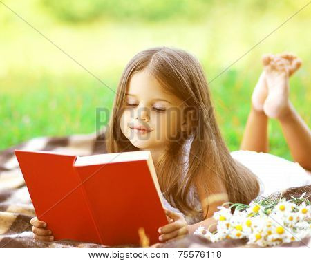 Child Reading A Book On The Grass