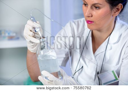 Nurse prepares IV solution for infusion.