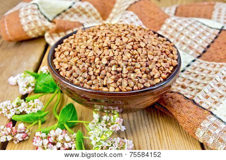Buckwheat in bowl with flower and napkin on board
