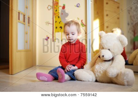 Little Girl Sitting On The Floor
