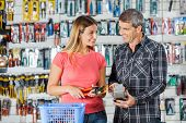 pic of pliers  - Smiling couple looking at each other while paying for pliers through smartphone in hardware store - JPG