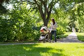 image of mother baby nature  - Full length of young mother pushing baby carriage in park - JPG