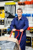 stock photo of trolley  - Mature worker in overalls pushing trolley in hardware shop - JPG