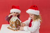 picture of gingerbread house  - Festive little girls making a gingerbread house on red background - JPG