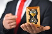 foto of hourglass figure  - Man in a suit with tie holding an hourglass