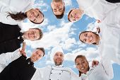 stock photo of huddle  - Directly below portrait of happy chef and waiters standing in huddle against sky - JPG