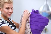 foto of dress mannequin  - Smiling fashion designer fixing dress on a mannequin - JPG
