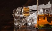 stock photo of obituary  - A close up of a whiskey bottle and shot glasses sitting on the obituaries section of the newspaper - JPG