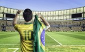 stock photo of flags world  - Brazilian soccer player holding the flag of Brazil celebrates with the fans on the stadium - JPG