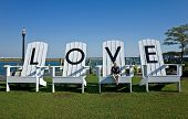 pic of lawn chair  - Woman sitting on a giant lawn chair in a public park inscribed with letters spelling LOVE - JPG