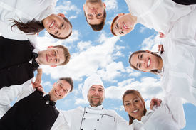 image of huddle  - Directly below portrait of happy chef and waiters standing in huddle against sky - JPG