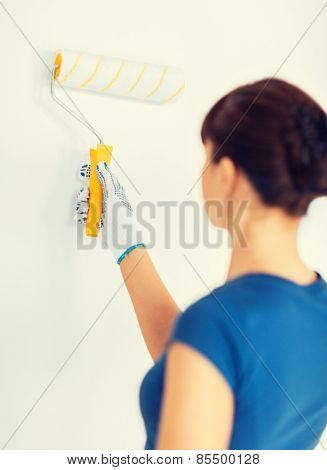 interior design and home renovation concept - woman with roller and paint colouring the wall
