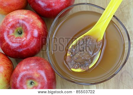 Fresh apples and a bowl of raw and unfiltered organic apple cider vinegar with mother enzymes on a wooden background