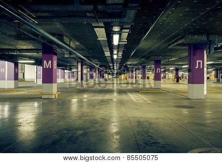 Parking garage underground interior, neon lights in dark industrial building, modern public construction