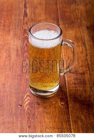 Glass of beer on the wooden grunge table.