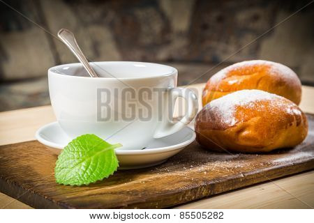 Tea cup with two buns on table