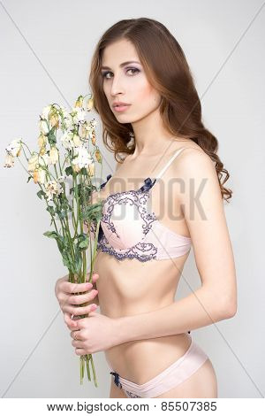 Romantic woman posing with dried flowers.