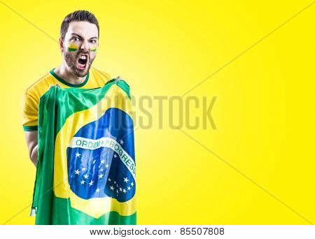 Man holding the Brazilian flag on yellow background