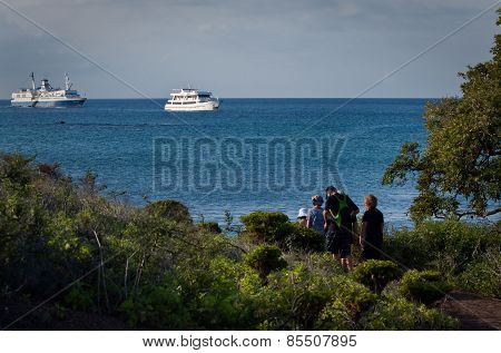 Tourists overlooking cruise ships from an island, Galapagos