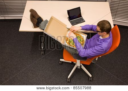 fast meal in office - man sitting at with legs on the desk, heaving break for pizza