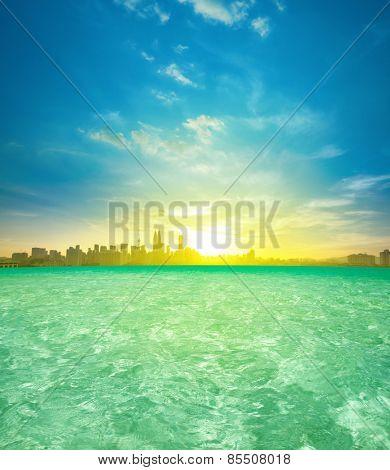 Kuala Lumpur city center sunrise view from luxury infinity swimming pool, beautiful natural golden sunlight.