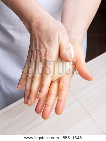 Woman's hands knead dough.