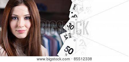 Young woman against the background of clothes and discount labels. Good  shopping concept