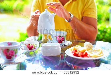Man Pouring English Tea In Cup, At Summer Garden
