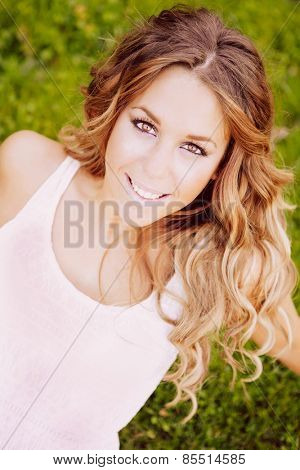 Cool pretty woman with white dress an a beautiful smile on the grass