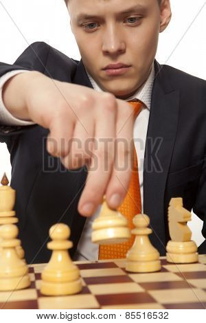Young business man moving chess figure