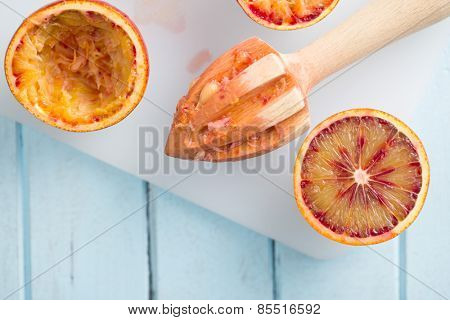 top view of halved blood orange and juicer